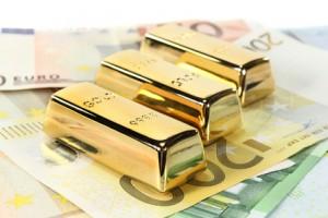 Goldbarren und Euronoten vor hellem Hintergrund